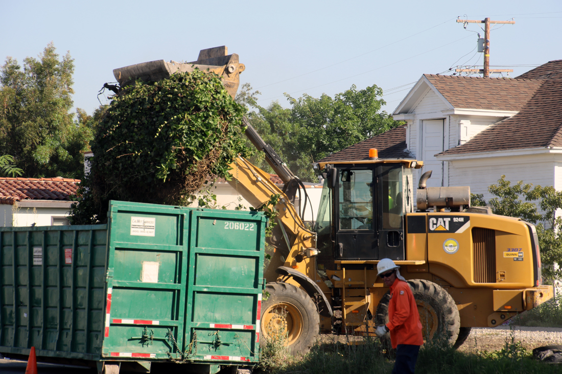 Crews dispose of a perimeter fence that collapsed due to overgrown vegetation. Photo by Eric Pierce