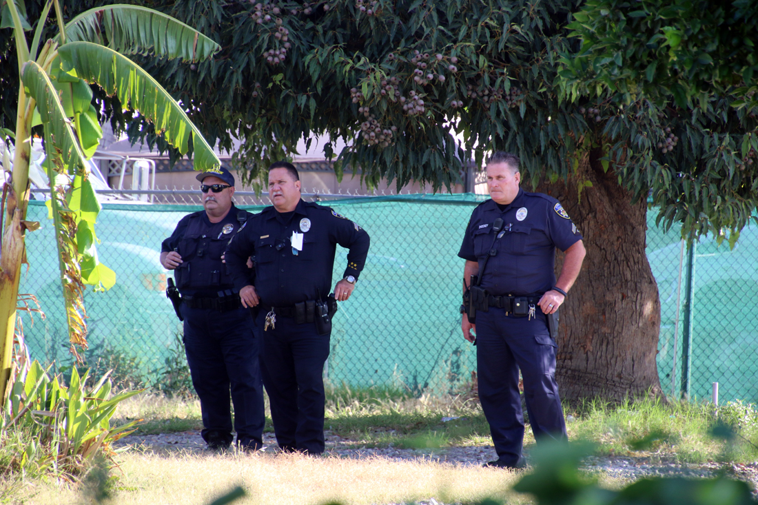 Police officers monitor clean-up efforts at the Rives Mansion on Wednesday. Photo by Eric Pierce