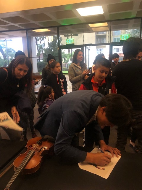 Students surround one of the Villalobos Brothers in the Downey Theatre lobby, seeking autographs. Photo courtesy Downey Theatre