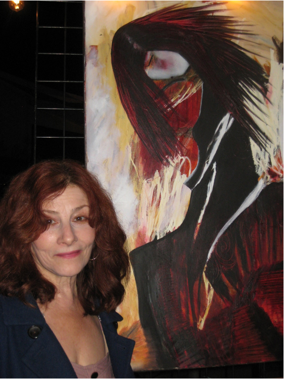 Monica Pucciarelli stands in front of one of her paintings. Photo by Lorine Parks