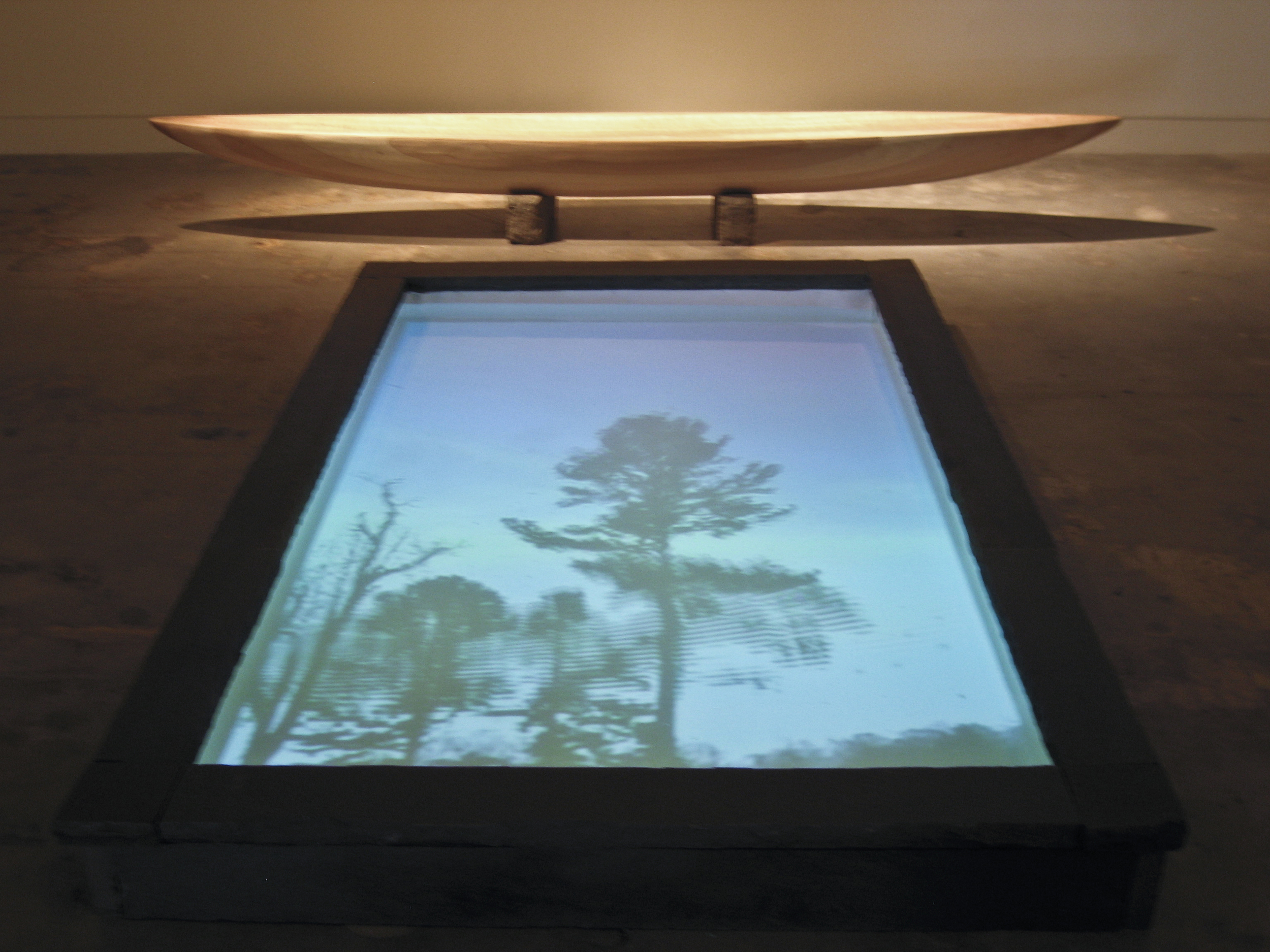 Quotidian Rift,   using sculptural elements and video, delineates its own physical environment, inviting the viewer to contemplate the nature of time and his/her own particular relationship to its passage.  These elements include: an iconic water vessel form carved in basswood, a shallow pool bound by layers of stacked slate, and a video projected from above into the pool of water below. Contents of the video include layers of sound and image referring to our experience of time, as its pace enables the viewer to savor the experience through gazing into the reflection pool.