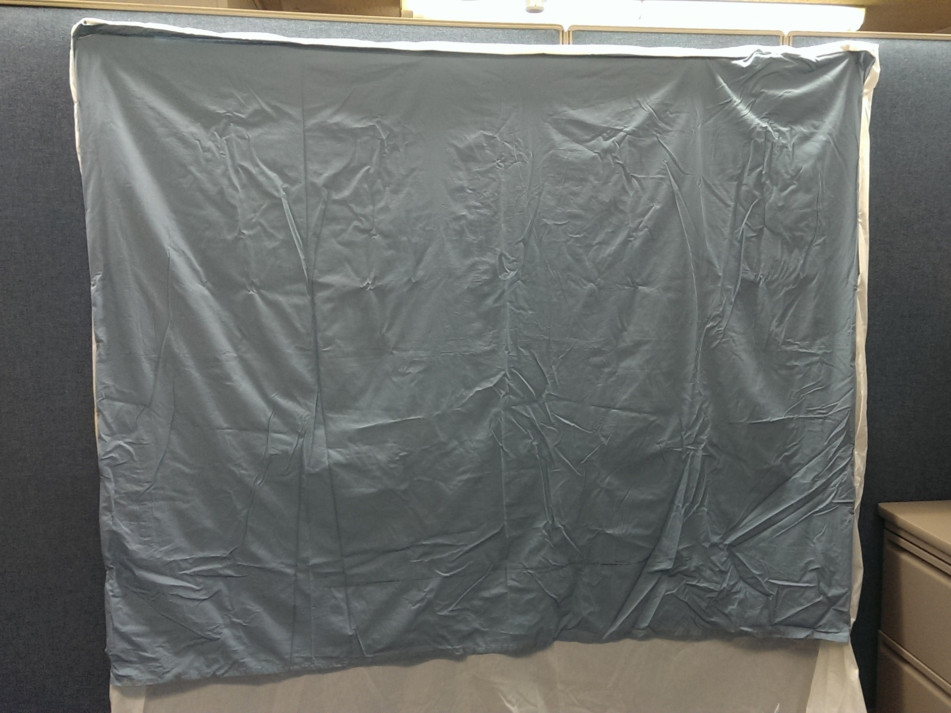 Hanging the sheet on the cubicle wall. Getting ready to paint