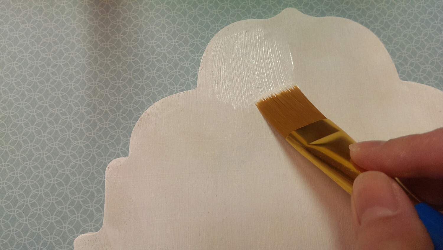 Applying the second coat of white acrylic paint to the wooden plaque.