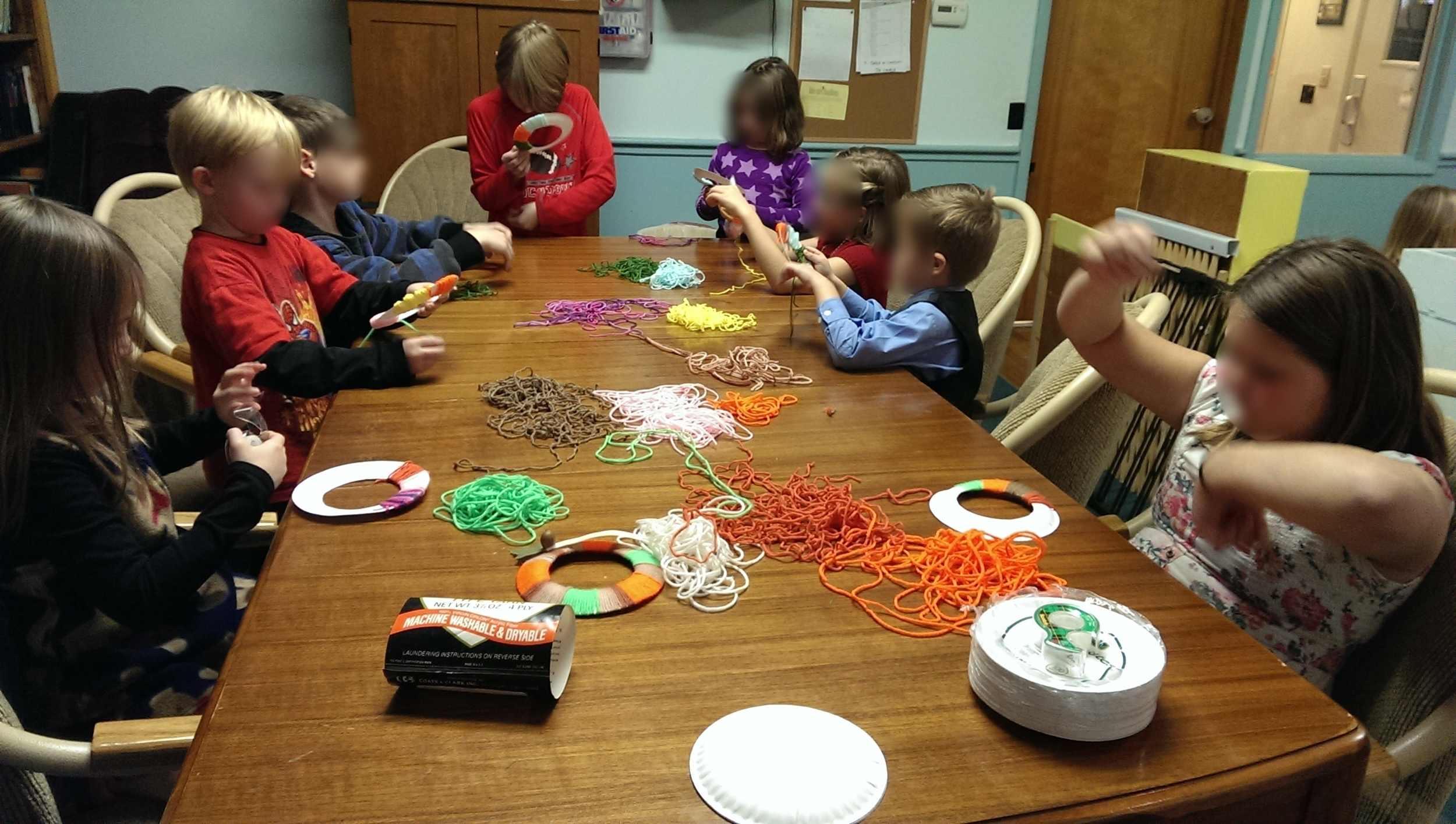 The kids are busily wrapping the yarn around their wreaths.