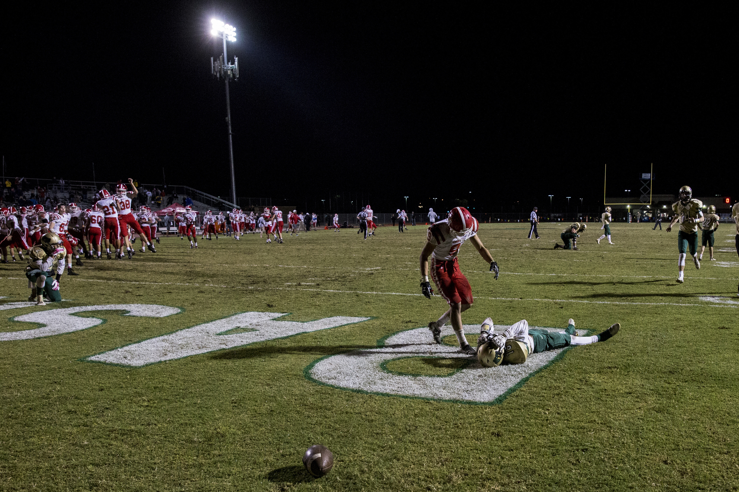 Brophy's Jimmy Hawkins goes to help up Basha's Terrell Brown after he missed a catch in the endzone during overtime at Basha High School on Thursday, Oct. 29, 2015 in Chandler, Ariz. Brophy won, 49-42.