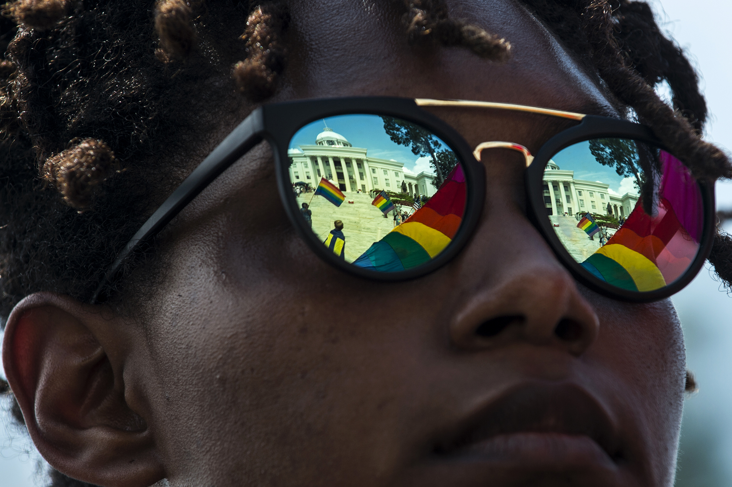 The Capitol building is reflected in Nikol Felder's glasses during the Montgomery Pride march on Sunday, Jun. 26, 2016 in Montgomery, Ala.