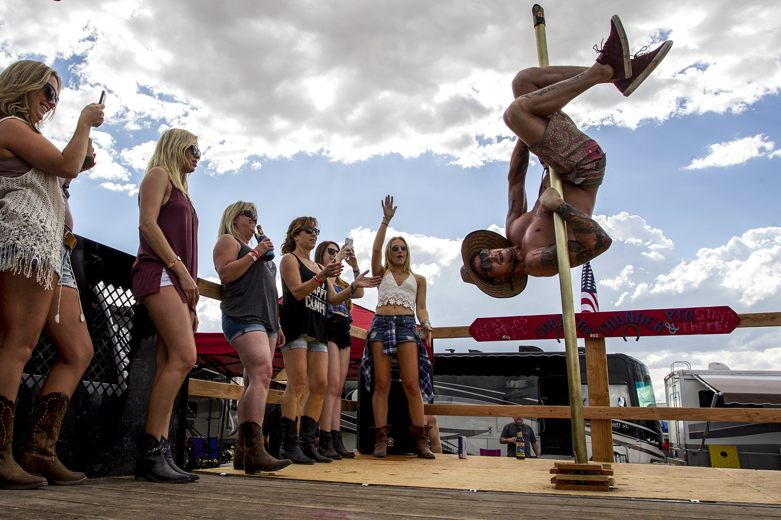 Michael Gereghcy goes upside-down on a stripper pole at a campsite during Country Thunder in Florence, Ariz.