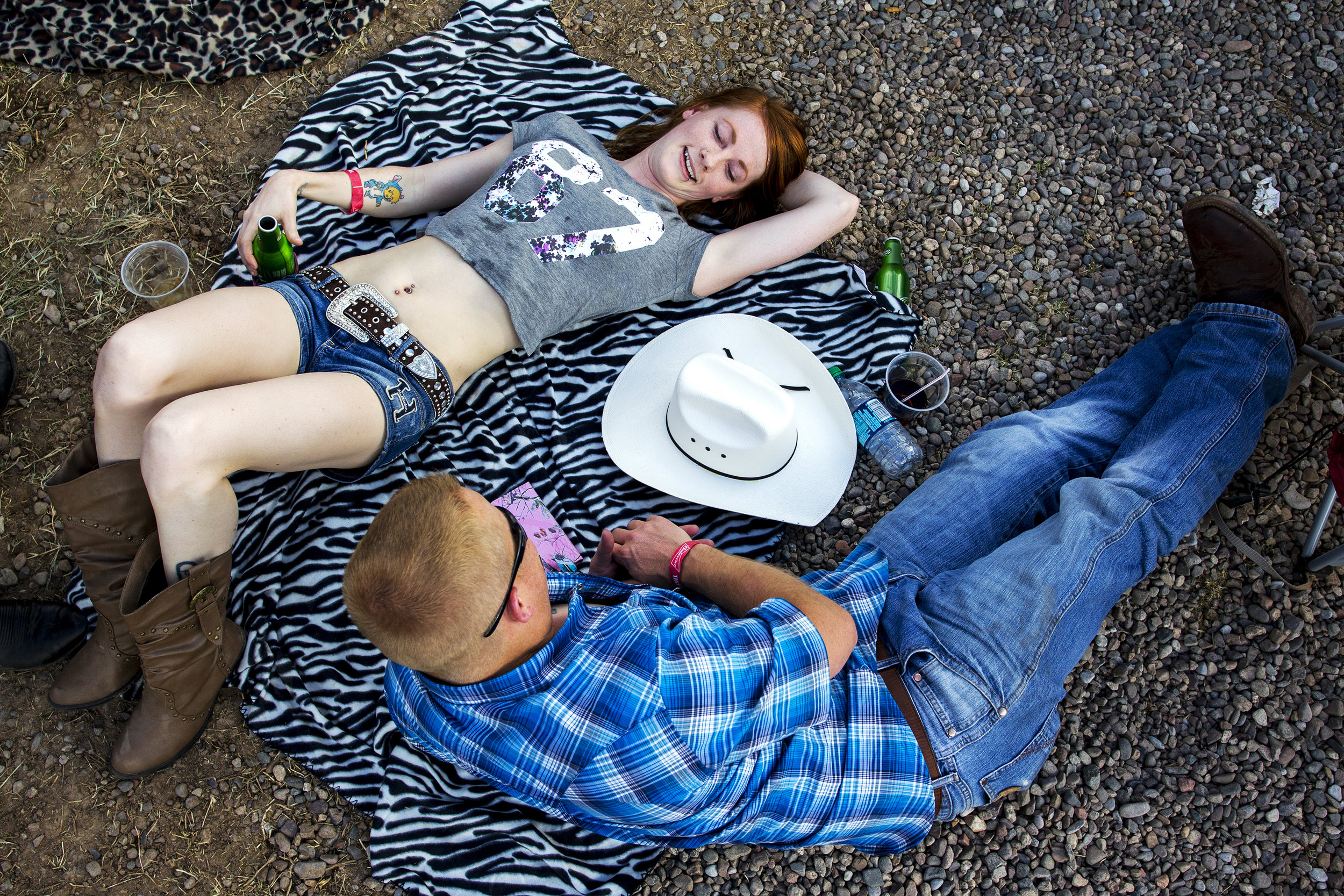 Tiffany Canniff and Scott Haack relax while Bryan White performs during Country Thunder in Florence, Ariz.