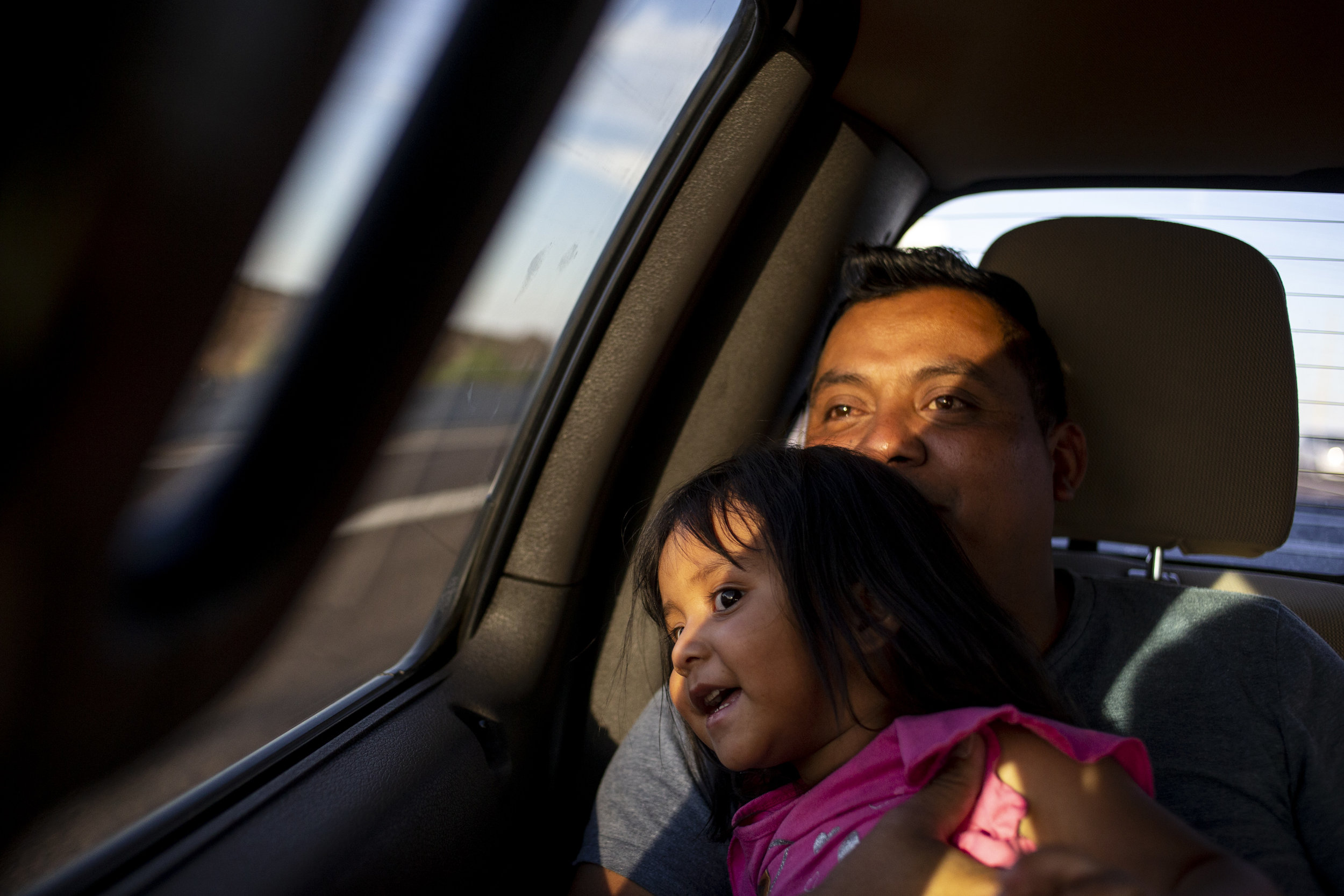 Jaime Escalante Galvez, 35, looks out the window with his daughter, Adriana Escalante Gonzalez, 2, on the way to Sky Harbor International Airport in Phoenix. Escalante Galvez migrated from Guatemala with his wife, Leydi Gonzalez Gonzalez, 29, and Adriana. They live in New Jersey and are applying for asylum.
