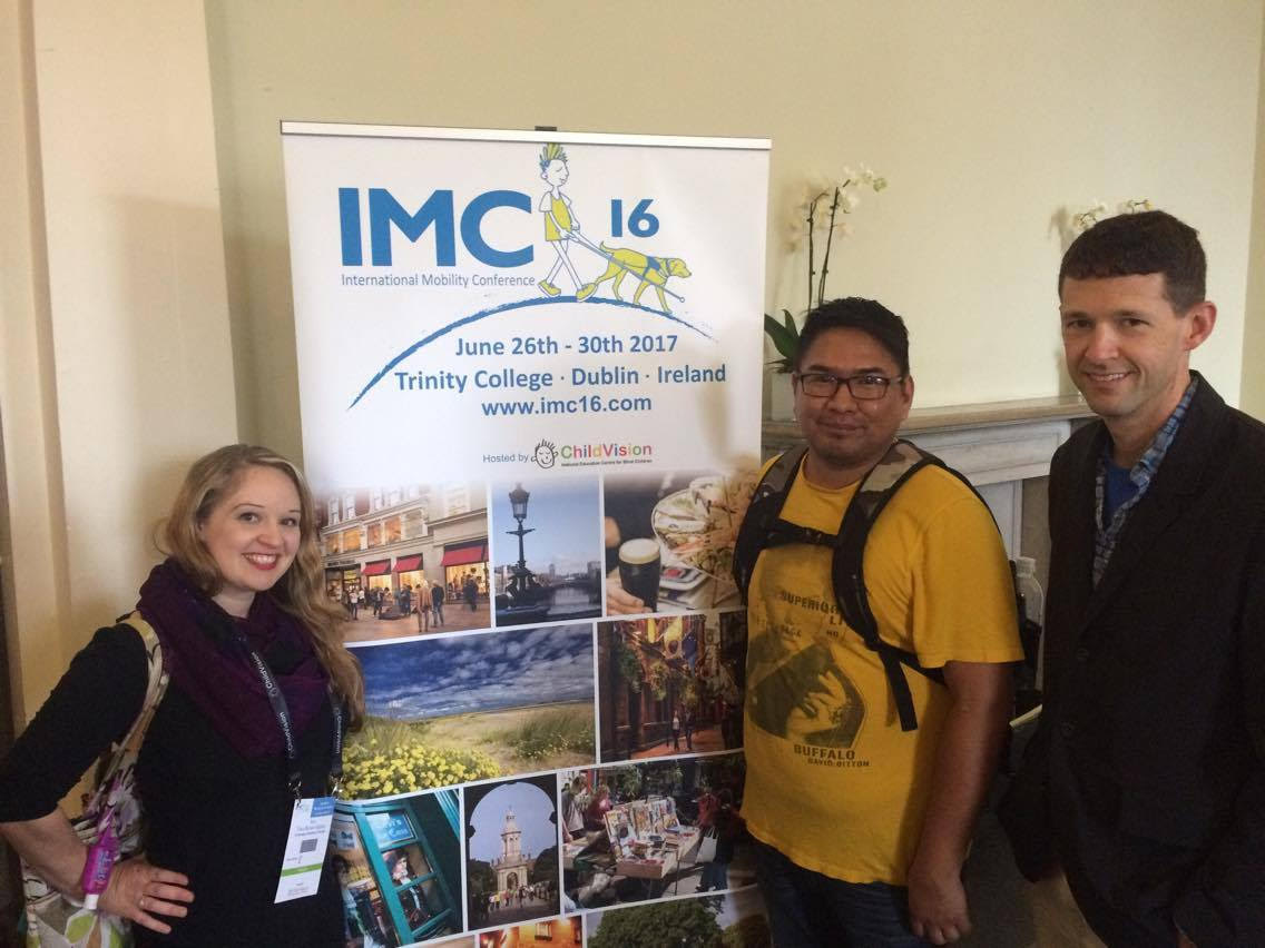 From left to right: Tara Brown-Ogilvie, Garrison Tsinajinie, and Kevin McCormack, standing in front of the IMC16 banner.