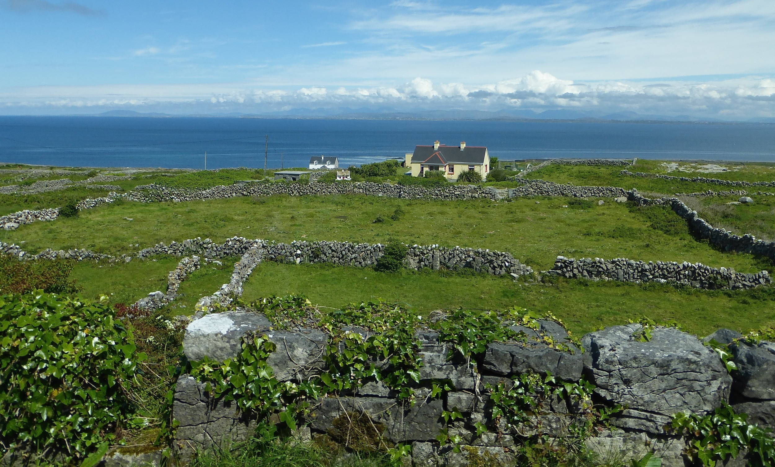The  Aran Islands , in the Atlantic Ocean off of Galway, are mostly limestone with a thin frosting of soil. Fields are divided by fences constructed from the limestones removed from the ground. Far across the water you can see the Twelve Bens (peaks) on the Connemara peninsula.