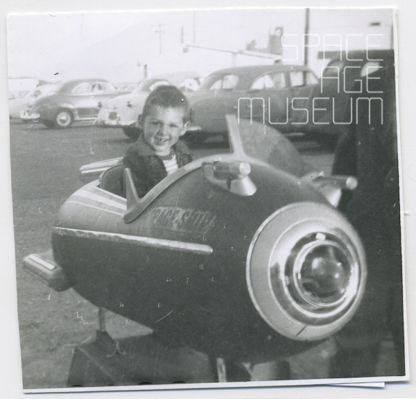 Boy in Coin-Op Space Ship near Parking Lot (1955)