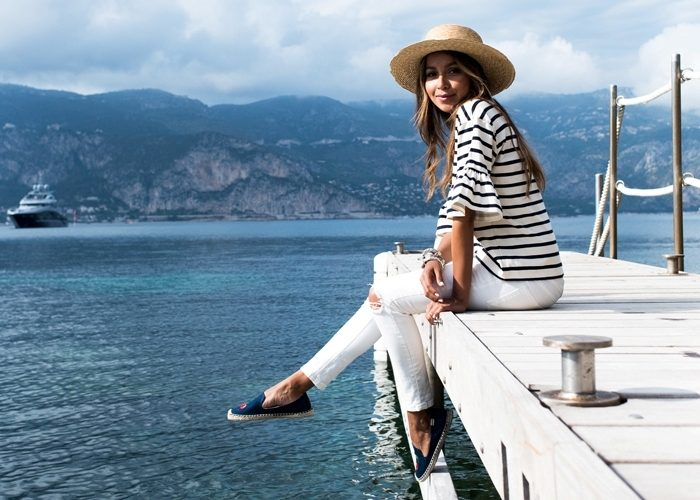 Julie Sariñana of @sincerelyjules on the dock of a Mediterranean bay wearing Soludos.