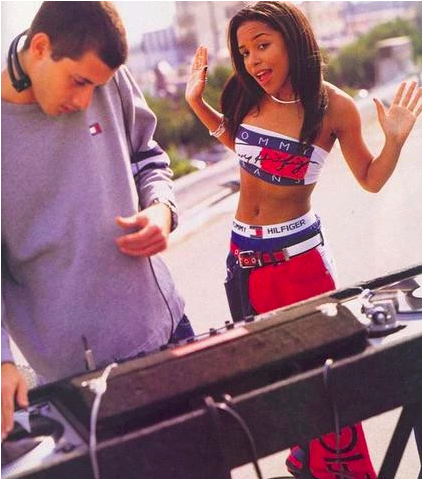 The late R&B singer Aaliyah and DJ Mark Ronson in full Tommy Hilfiger in 1996, one of the originating moments of celebrity endorsement and showcases the logo love of the time. Tommy's brother Andy Hilfiger cast her for the spot.