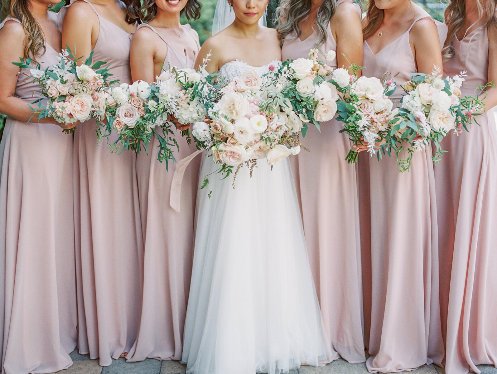 Bridesmaids in blush and dusty rose dresses