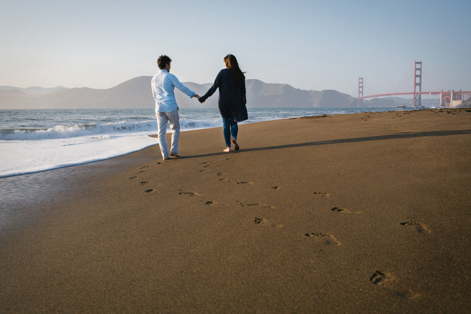 Footsteps in the sand during Baker Beach engagement photos with Neta and Pasha.