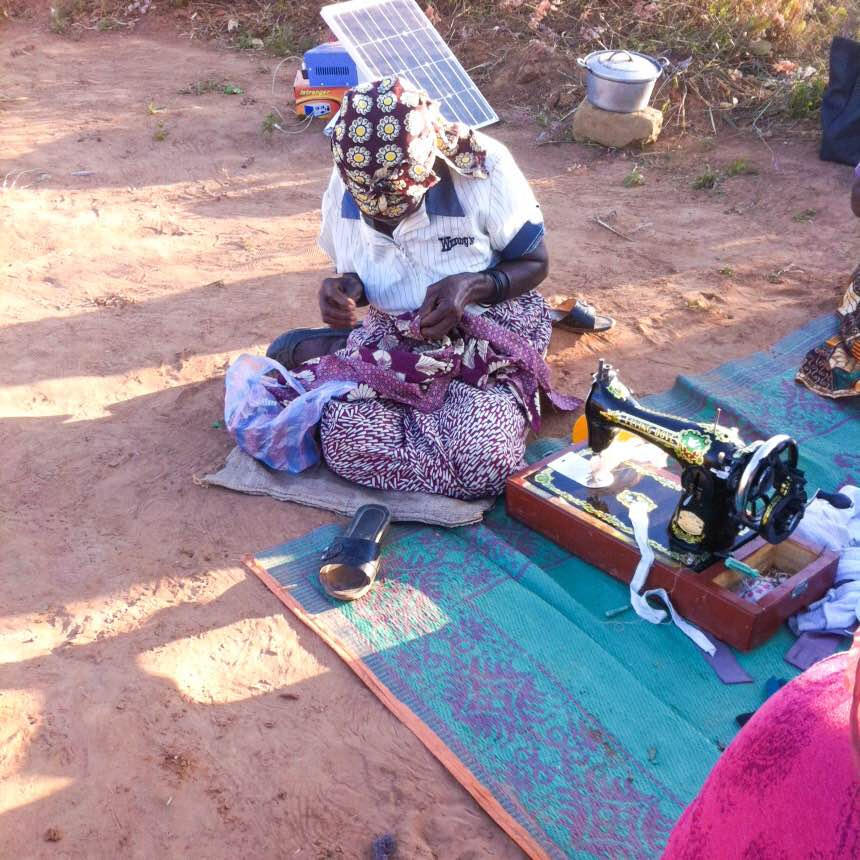 """The oldest woman of the village, who the ladies refer to as """"Sweet Sixteen,"""" hard at work using the manual hand sewing machine."""