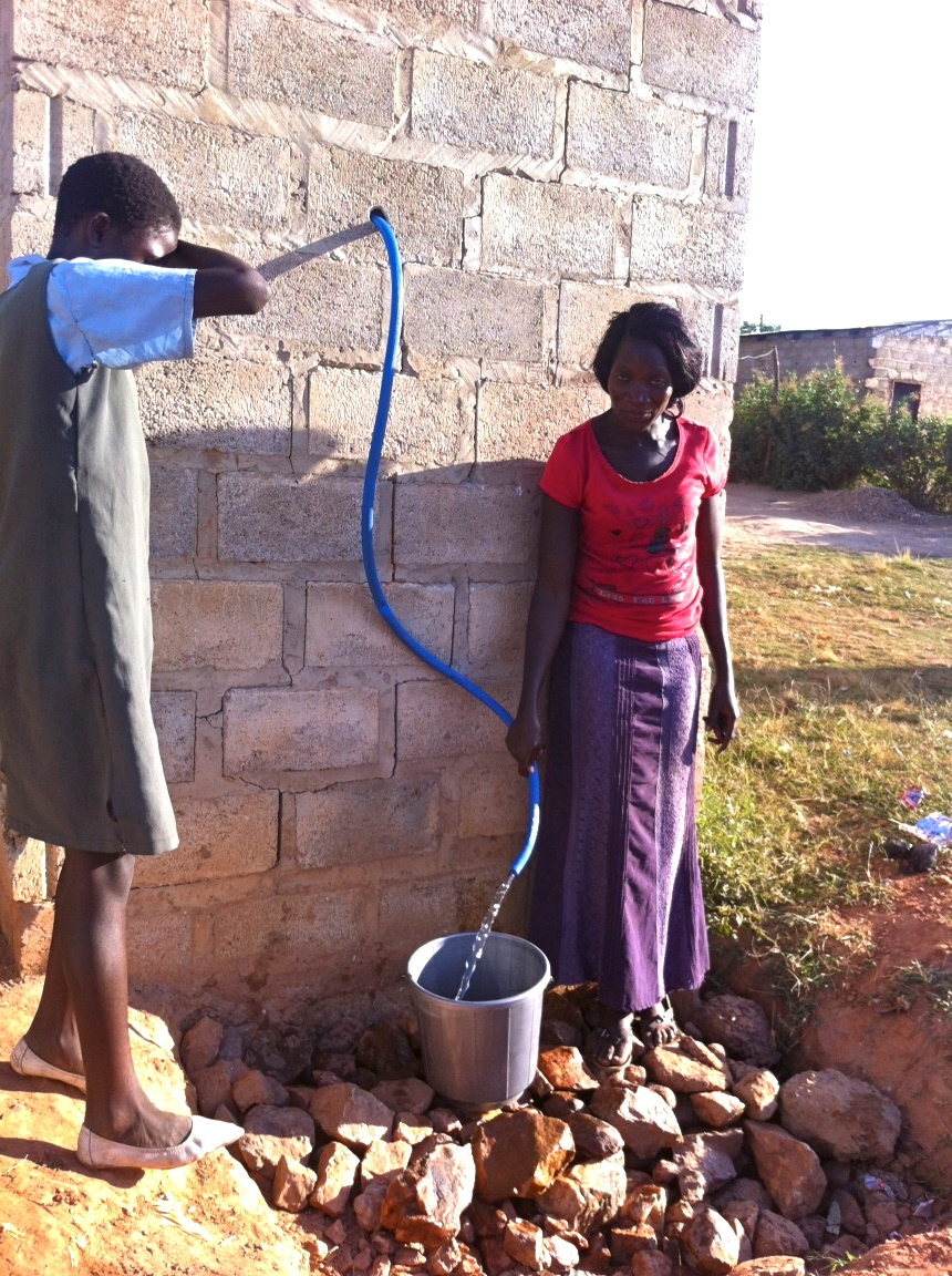 Yvonne dispenses water from our clean water well to this girl coming from school. Look how crystal clear that water is!