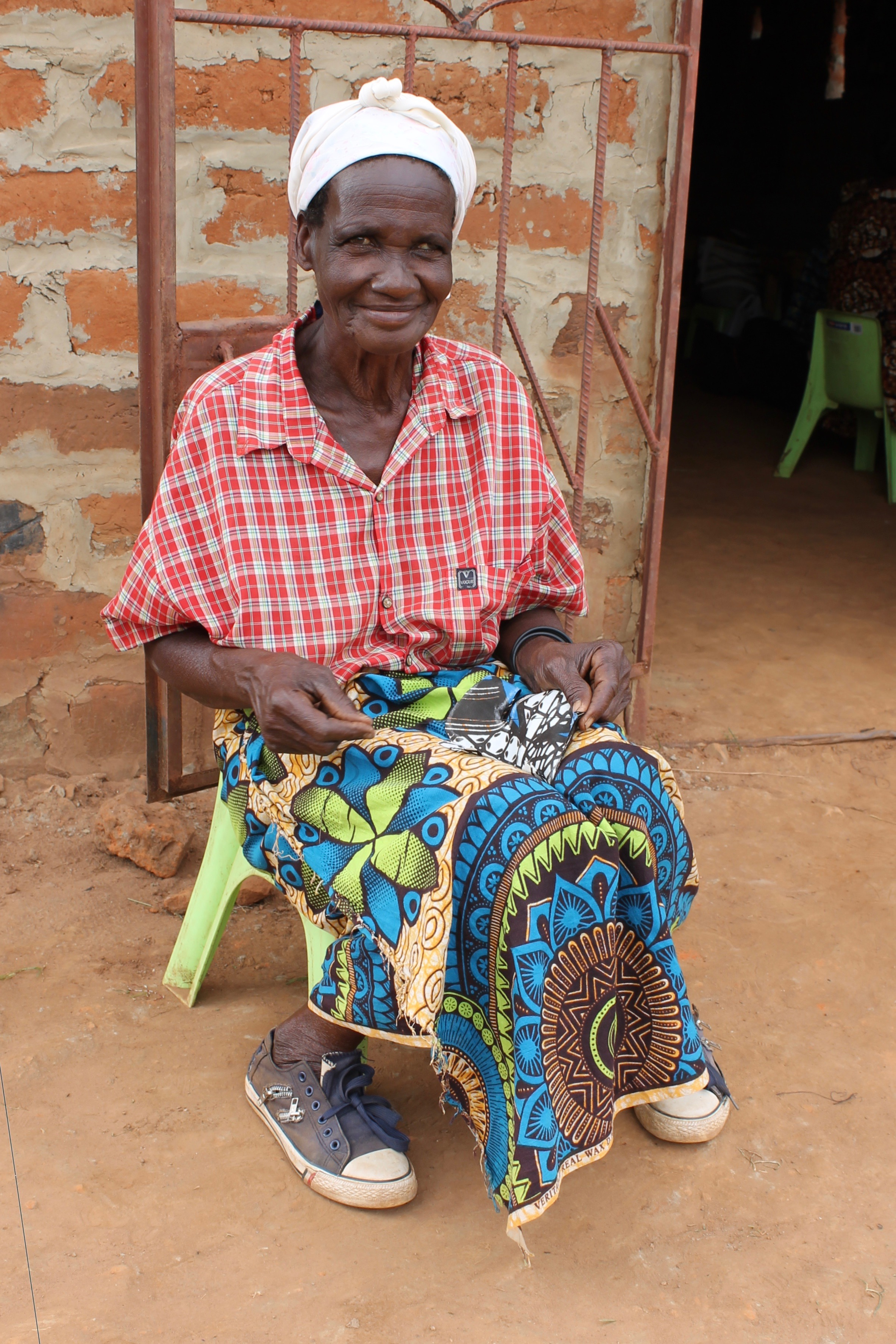Meanwhile, Elizabeth Muchochoma, oldest woman in Muchochoma Village at 55 years old, hand-sewed some product samples outside.