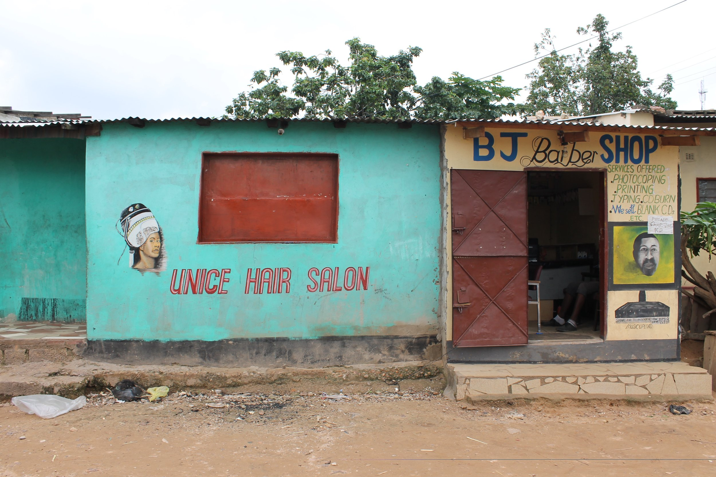 The middle and end shops outside Emeli's house, one rented out and one run by Emeli's son to prepare him to be a businessman in his community.