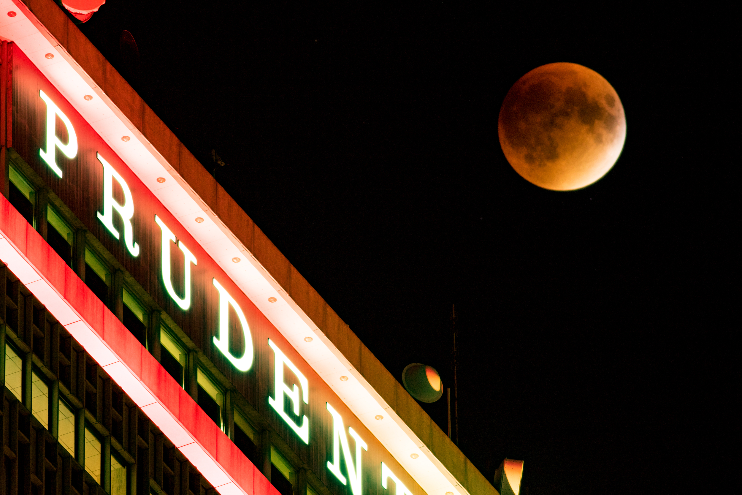 Close up the the moon over the Prudential Building in Boston