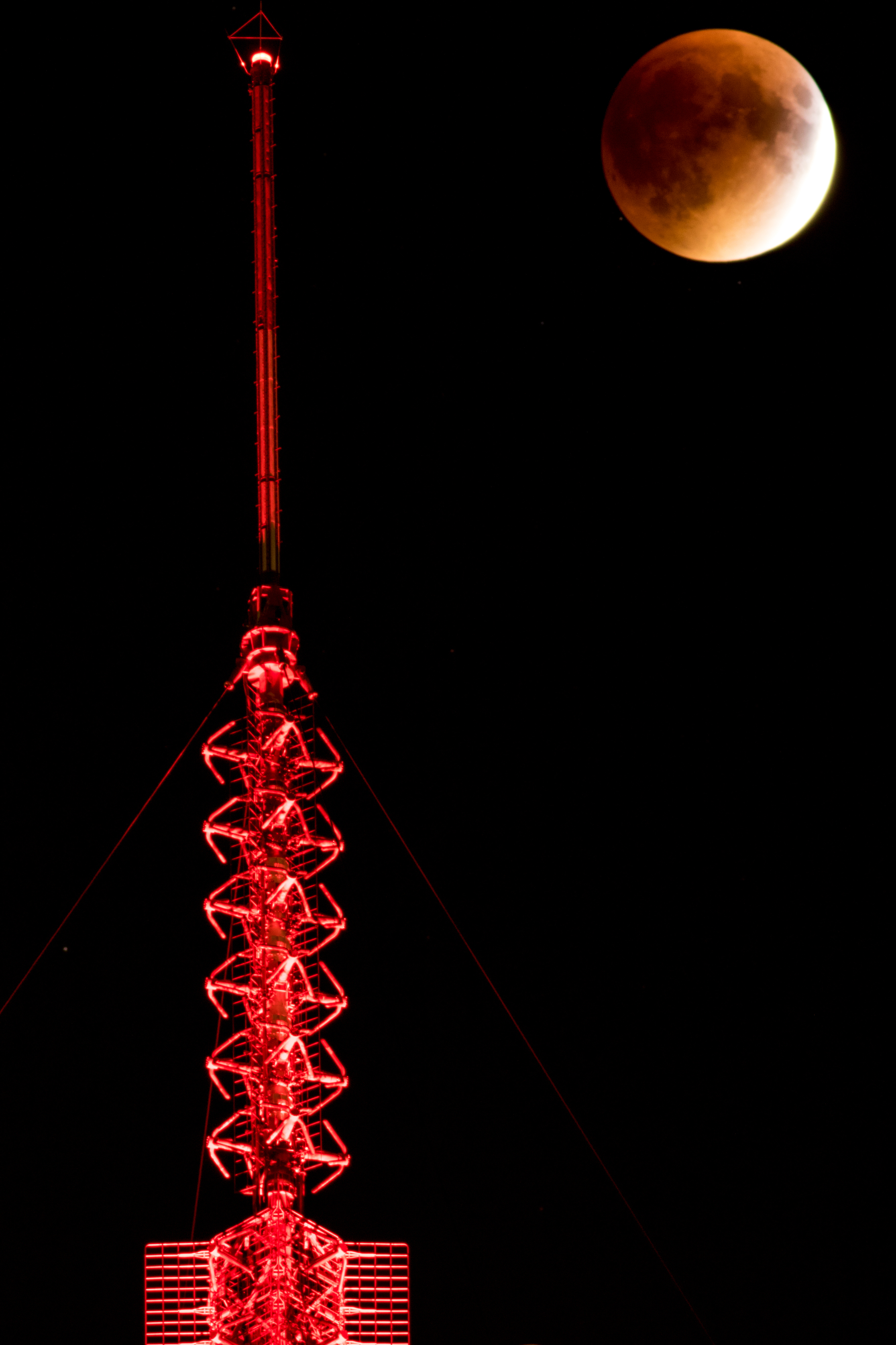The moon next to the antenna on top the the Prudential Building in Boston, MA