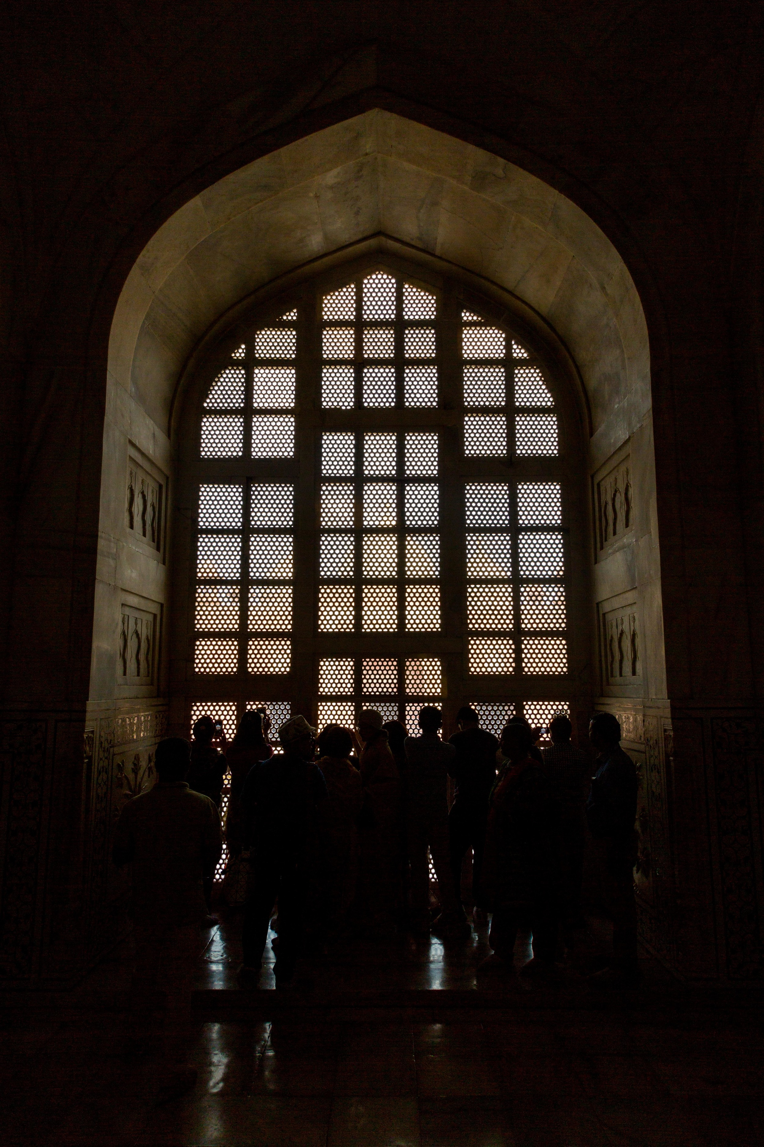 A crowd of people admire the Jali in the window of the Taj Mahal.  Jali is the stonework done to make it easier to see out than it is to see in.  The original two way mirror.