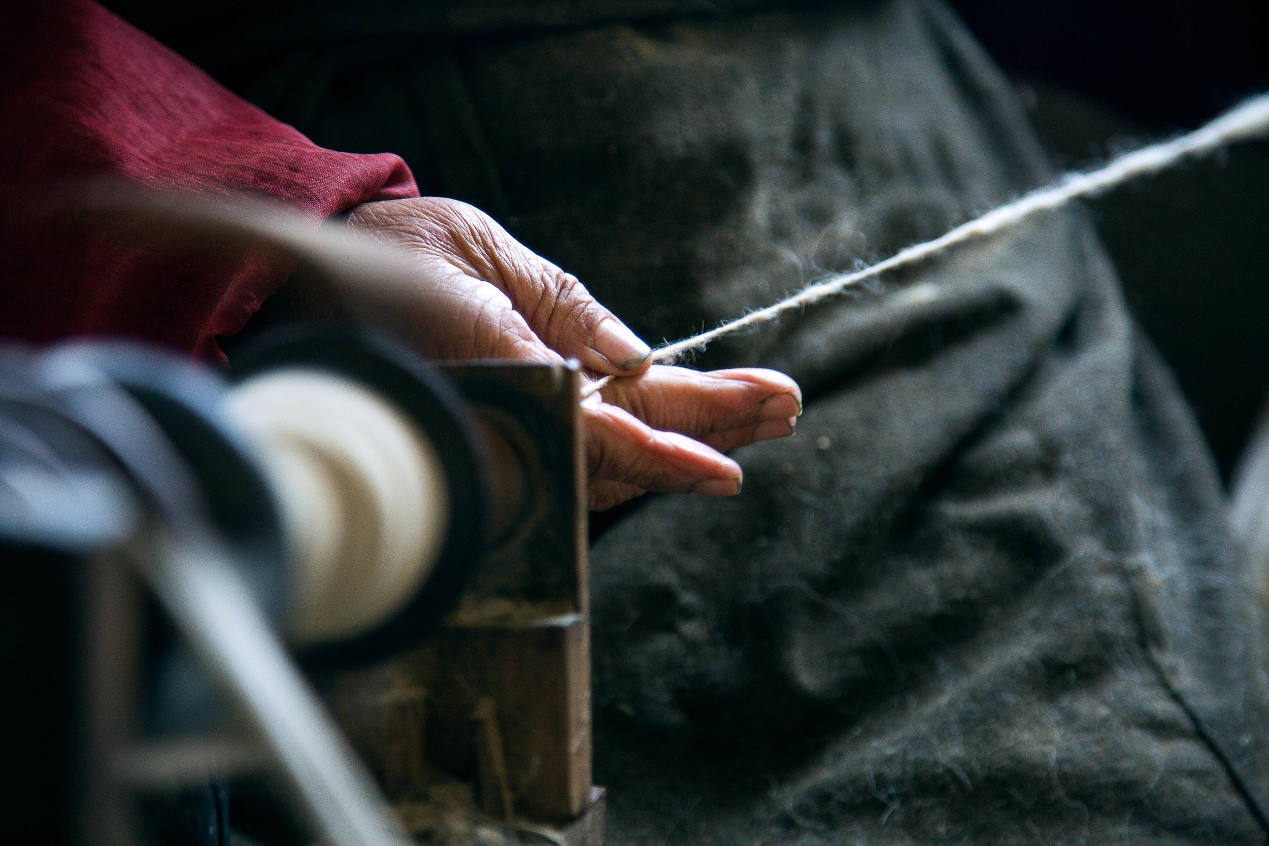 A women turning sheep wool into yarn at the Tibet Relief Center in Darjeerling, India.