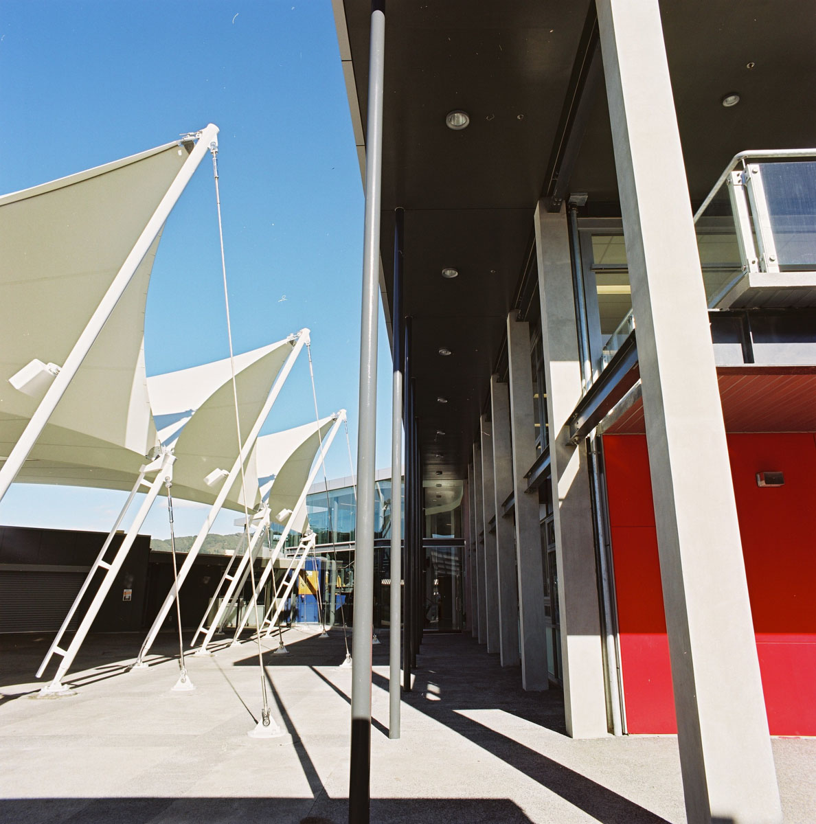 """Located at the front entry heart of the campus, the design draws reference to the traditional school """"cloistered edge"""" yet in a modern vernacular.  A simple smooth steel skin plate punctuated centrally at the entry by a recessed curtain wall greets first time visitors. On the opposite side, a transparent edge engages the sheltered plaza. A double height transparent atrium linked at the upper level by a floating bridge structure, internally separates building structure and function.  A sheltered multi purpose gathering space for students was an essential requirement of the brief. A Plaza was created and flanks the new Administration Building. A tensioned membrane canopy structure covers some 1,000sqm to create an indoor/outdoor space providing shelter from all weather conditions."""