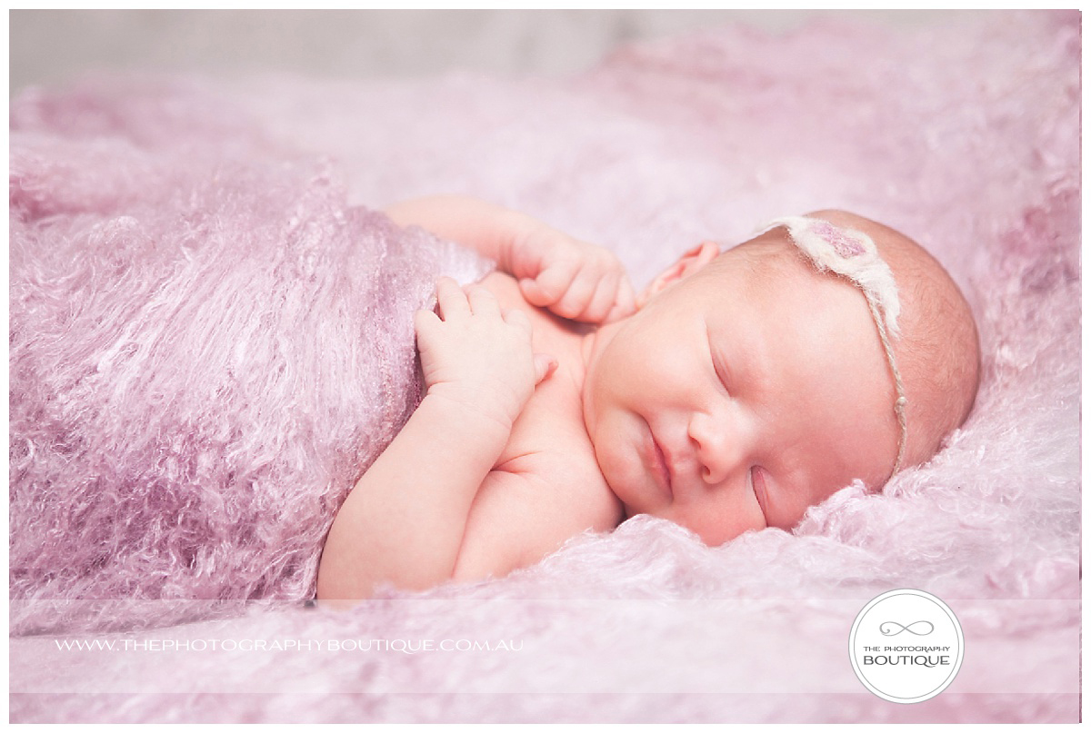 newborn sleeping relaxed pose with pink wool blanket