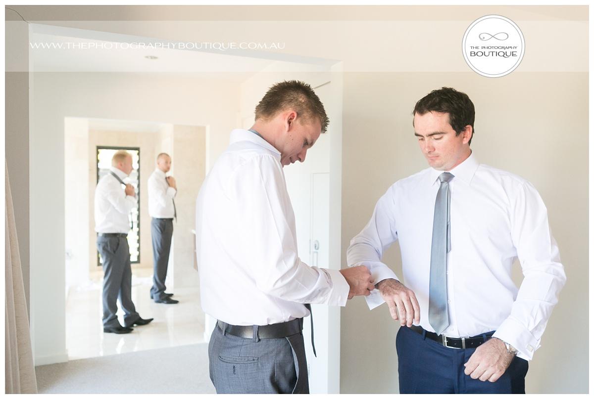bestman helping groom put on cufflinks