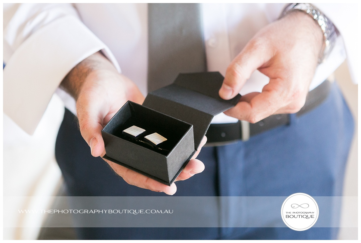 groom holding cufflink box