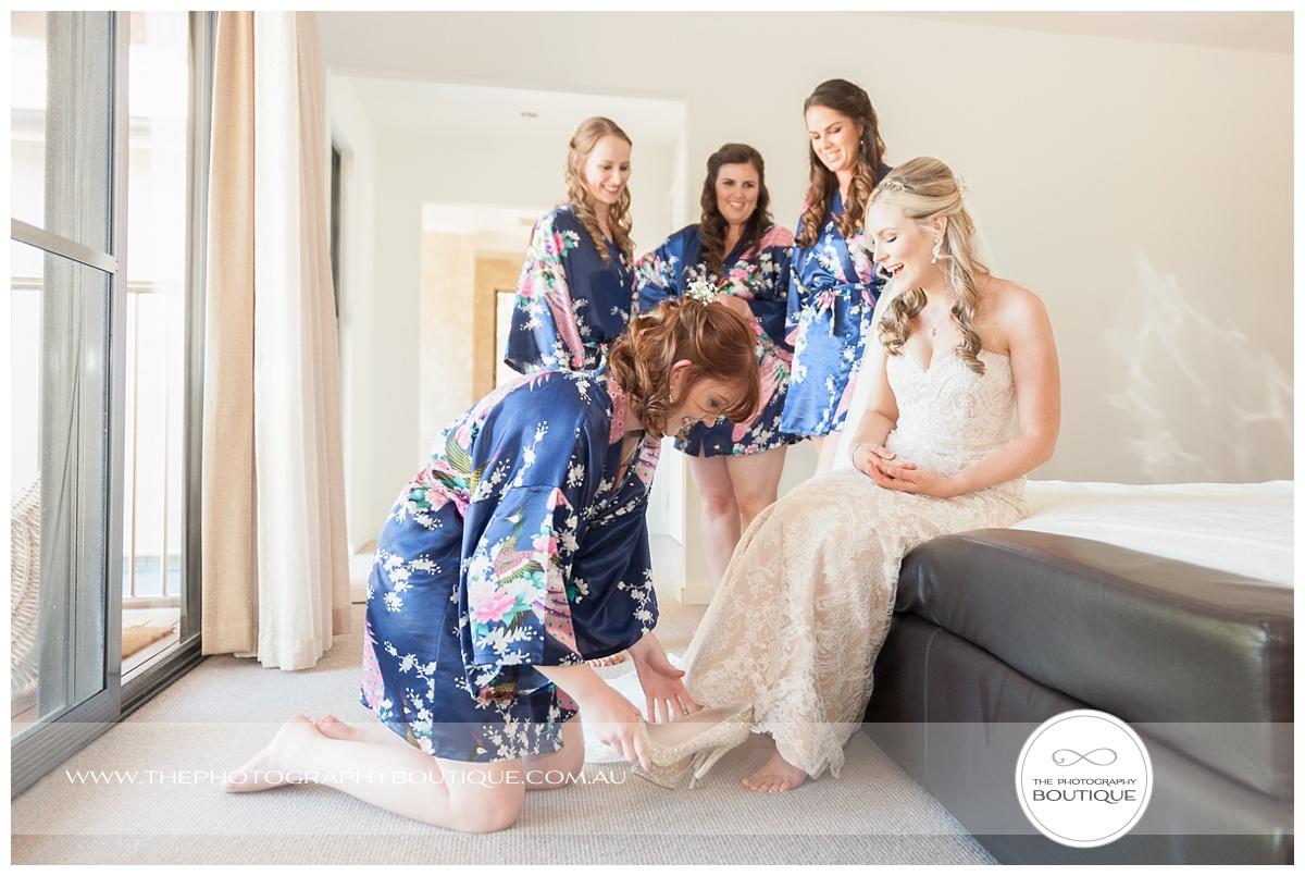 bridesmaids putting brides shoes on