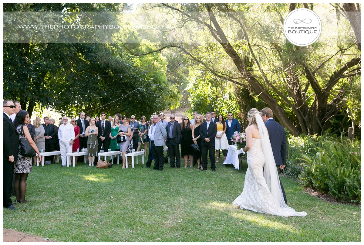 walking down the aisle in the garden at chandeliers on abbey margaret river
