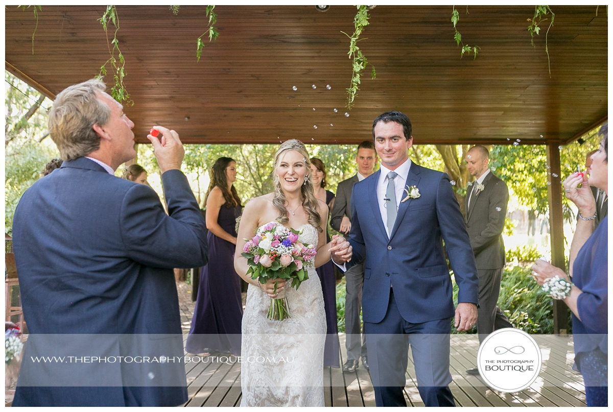 guests blowing bubbles as bride and groom walk back down the aisle at chandeliers on abbey margaret river