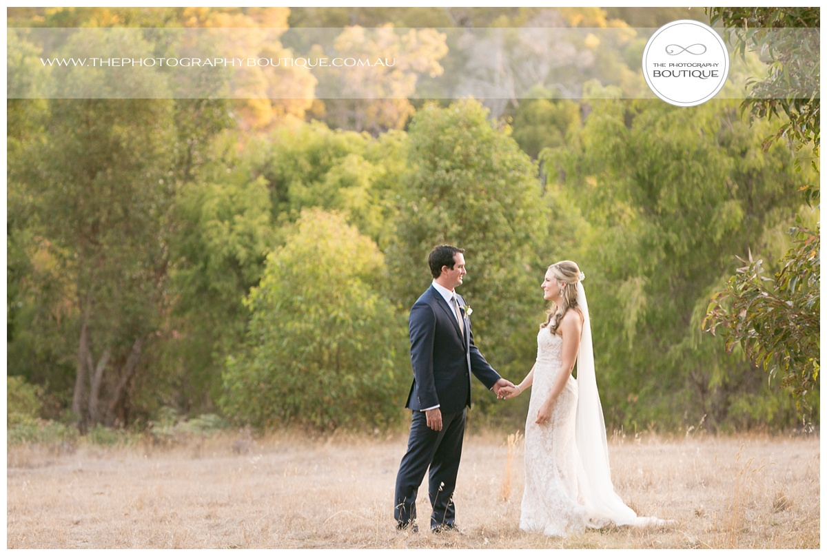 bride and groom holding hands in a margaret river paddock