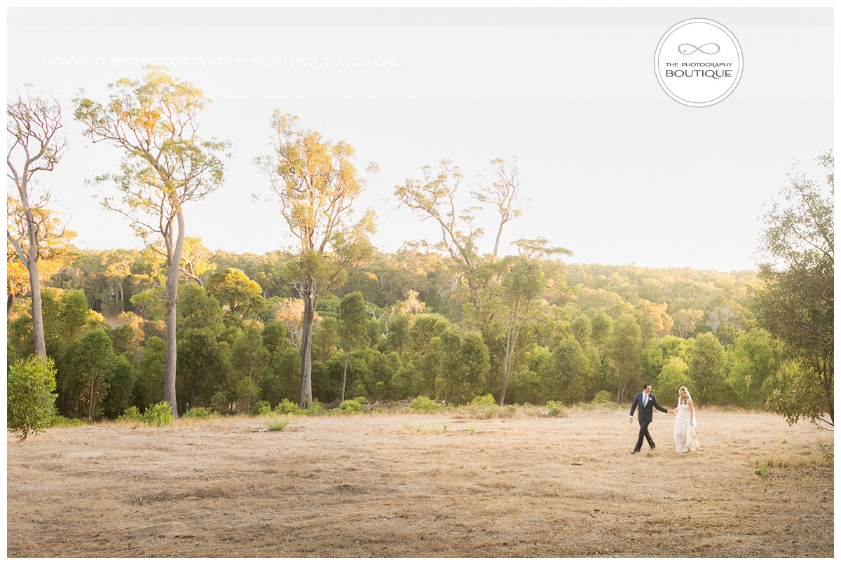 groom leading bride by the hand through a margaret river paddock
