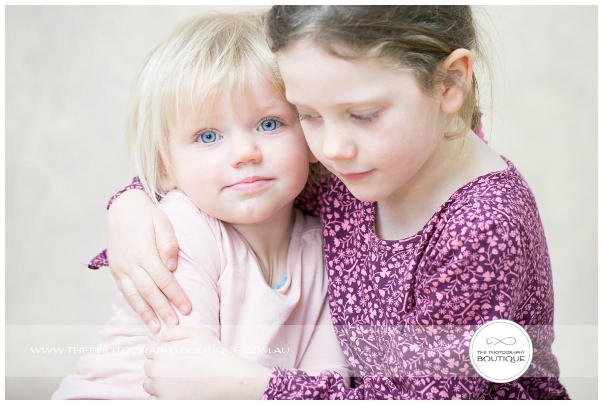 Big sister hugging her baby sister