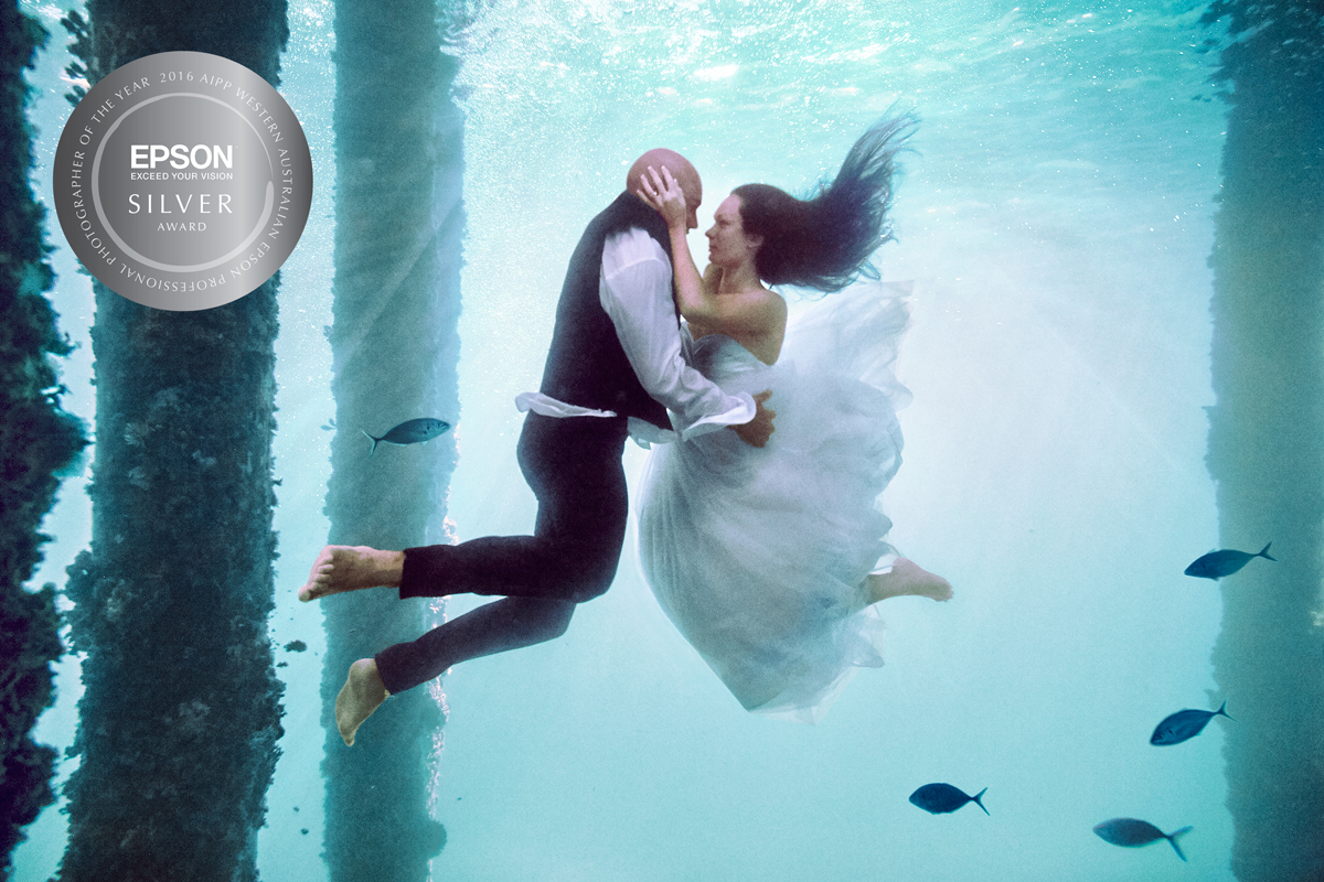 About this image:  This image features the gorgeous Carli and Shae, who's wedding we photographed last year. When they came to meet with me about their Big Day they asked if we could forego the engagement session we usually include in our wedding pakcages, and do an underwater trash the dress shoot instead, as they have lived their whole lives in and on the water and it would have special meaning for them. So we planned and prepared and I spent an afternoon in scuba gear (with my lovely assistant Bianca) at the end of Busselton jetty and this is what we got, which I was super happy with. Evidently lots of other people liked it too as it went viral and was published around the world! I'm absolutely stoked my fellow professionals also recognise it as an award winning image, and I hope it will be the start of a new journey to always challenge myself and be up for doing something different!