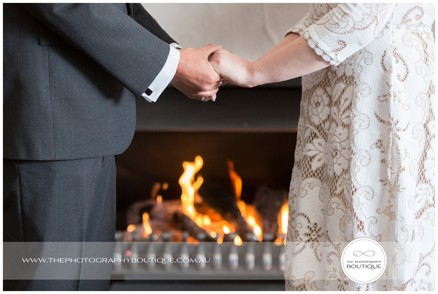 Bride and groom holding hands in front of the fireplace at Caves House Yallingup