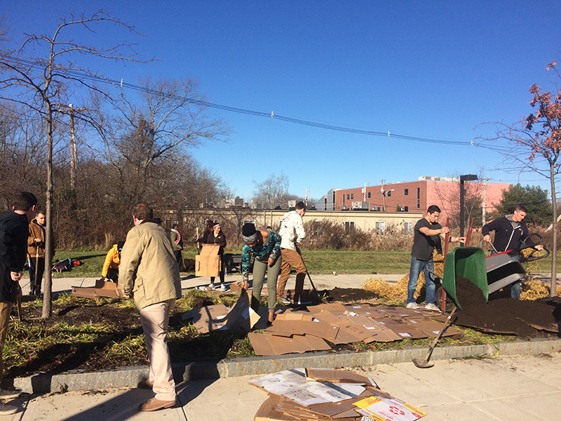 Students and faculty cover a raised garden bed with organic materials to prepare for spring planting.
