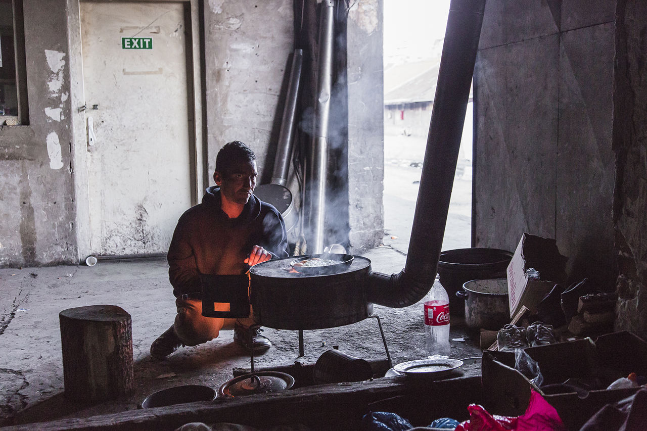 A refugee preferes to cook his own meal inside one of the barracks. The refugees feel to be tollerated by the serbian people and authorities
