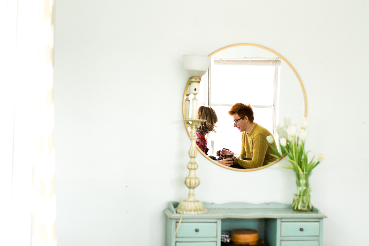 couple reflected in a bedroom mirror during an intimate in-home couples session in Kansas City, MO