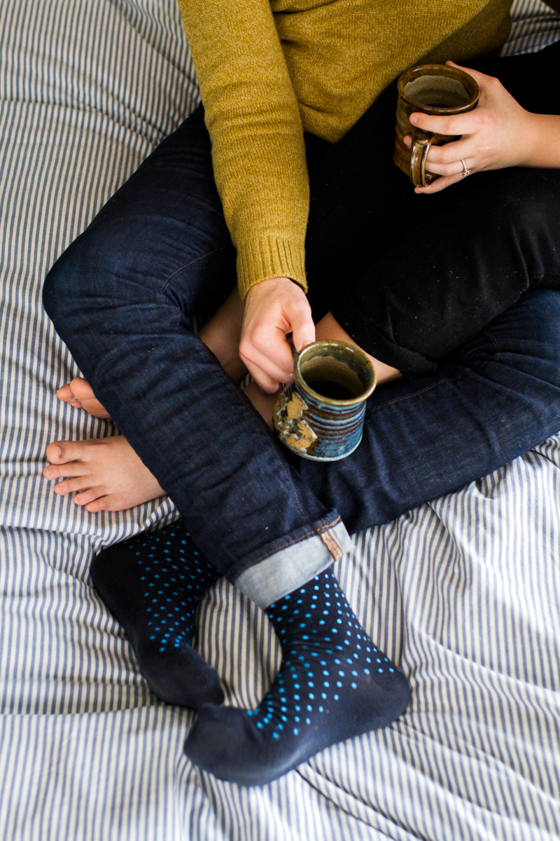 cuddling together with coffee on a bed during an intimate in-home couples session in Kansas City, MO