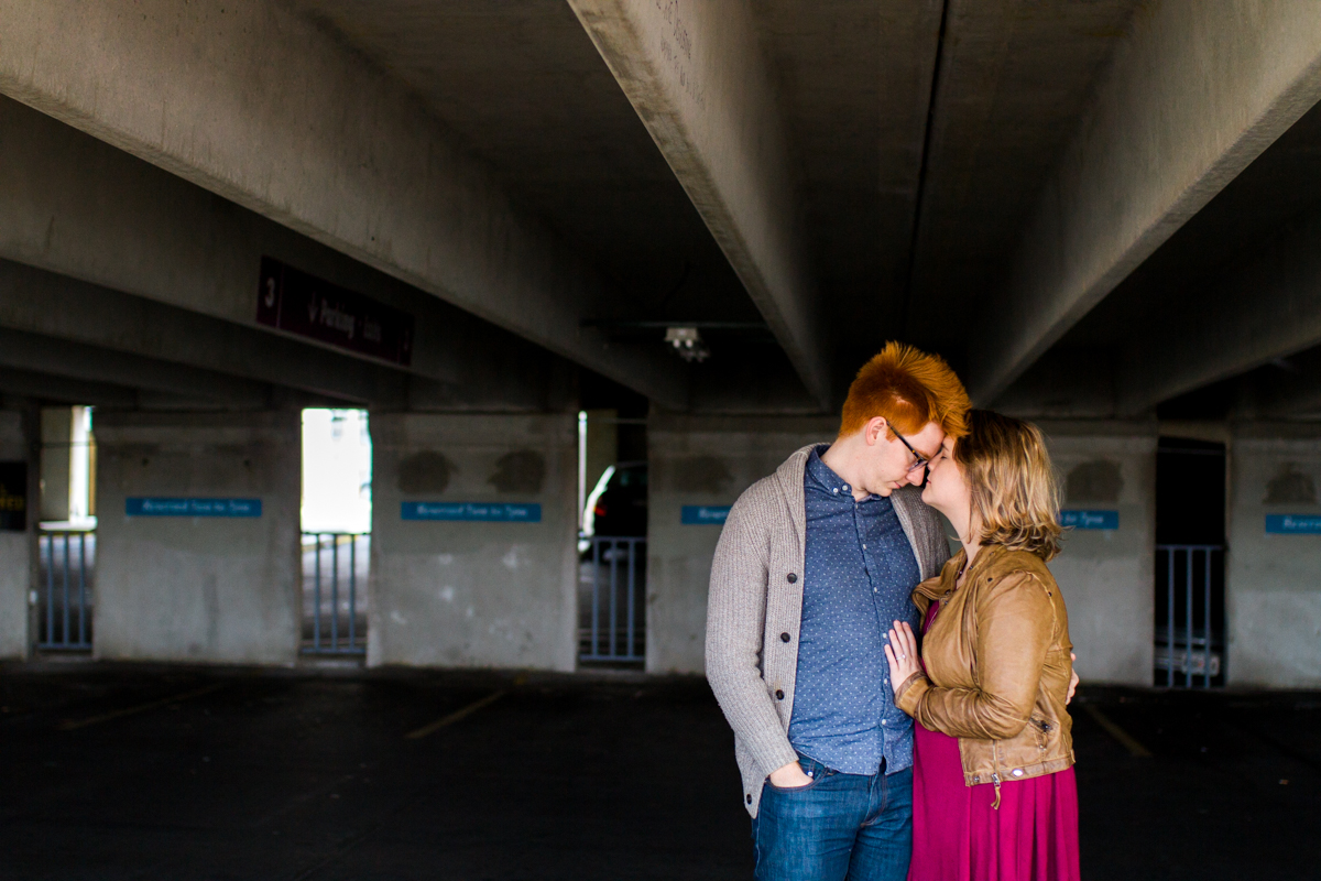 engaged or married couple cuddle in a parking garage in Westport Kansas City, MO