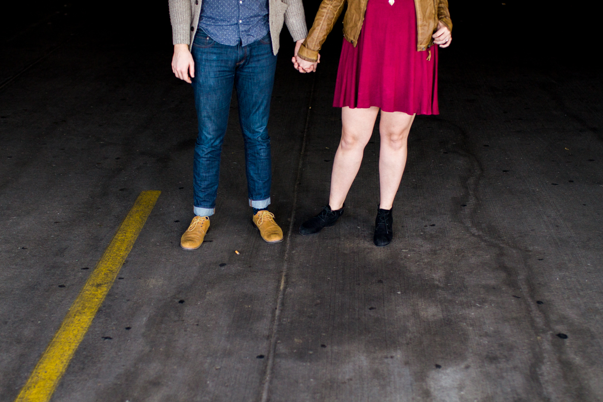 engaged or married couple holding hands in a parking garage in Westport Kansas City, MO