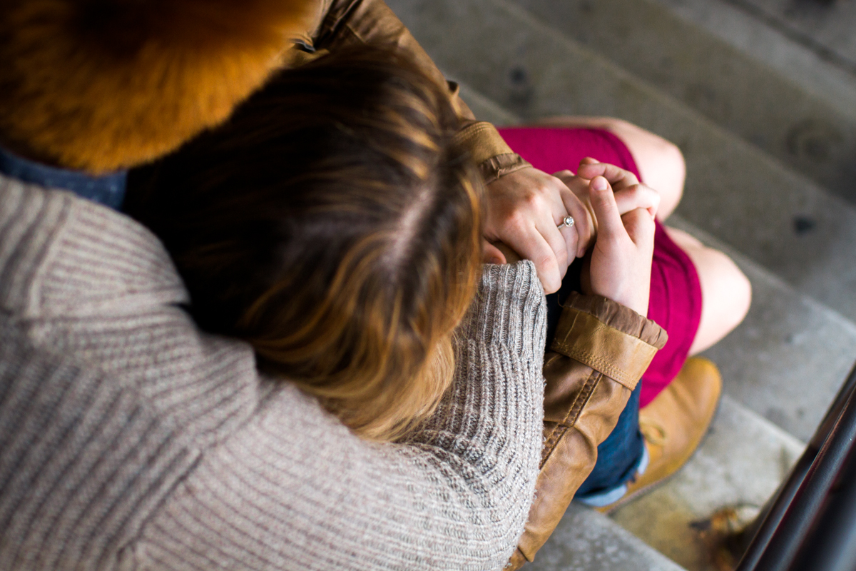 engaged or married couple cuddle in a parking garage in Westport Kansas City, MO engagement ring
