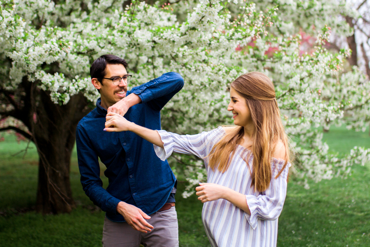 Kansas City Loose Park spring maternity session dancing by the flowering apple tree Kansas City maternity photographer