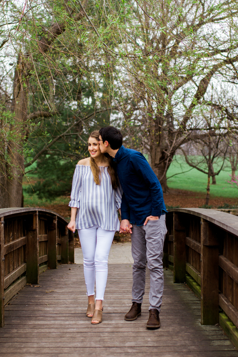 Kansas City Loose Park spring maternity session walking across the bridge holding hands Kansas City maternity photographer