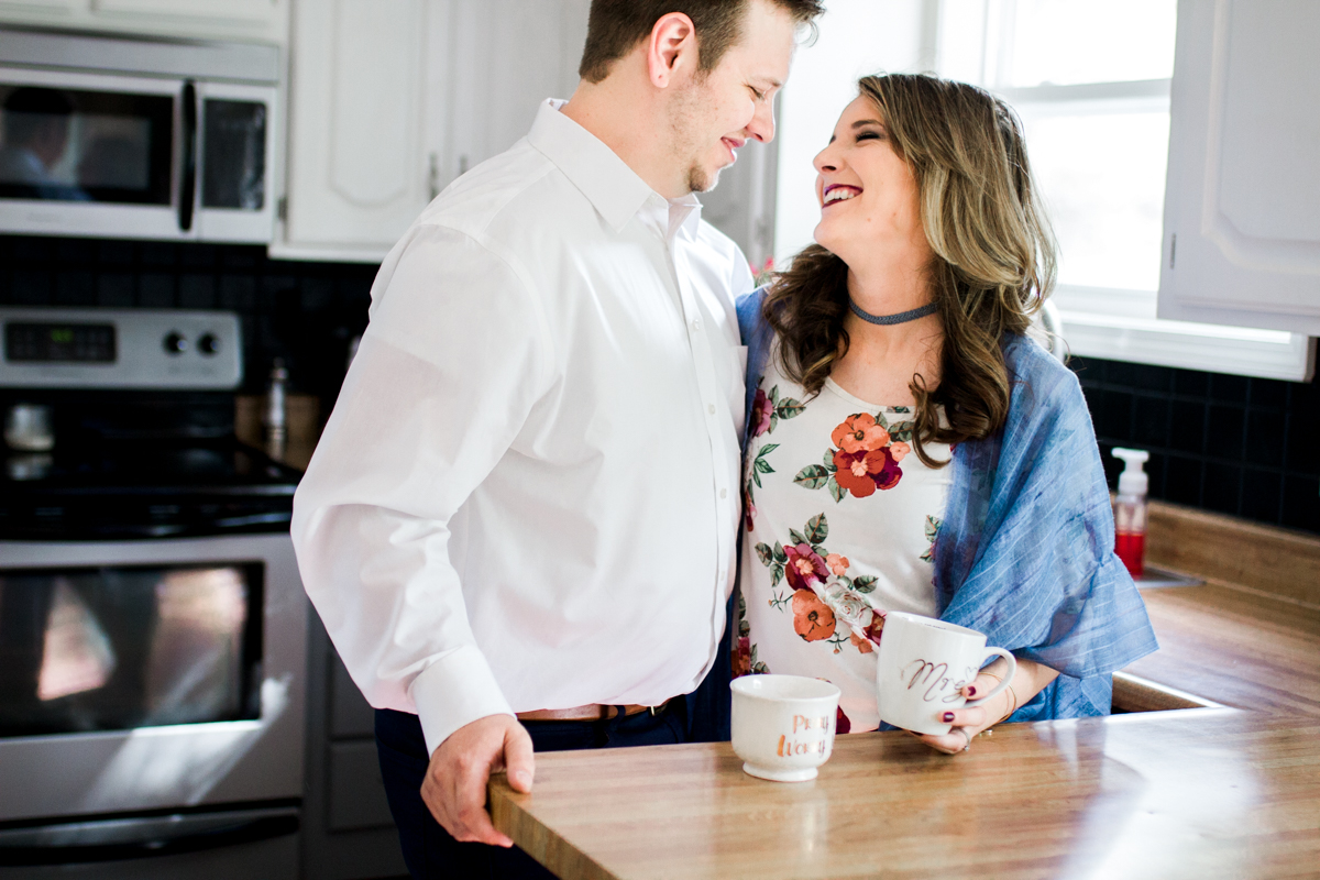 Kansas City lifestyle photographer in home couples session cuddling in the kitchen with coffee engagement photos black and white photo